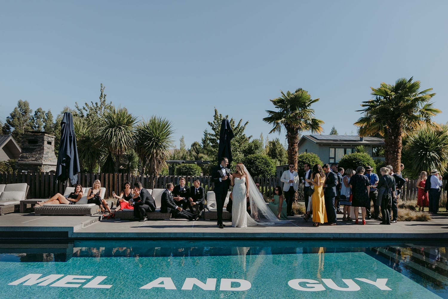 Vinka Design Features Real Weddings - bride in custom made gown, a combination of our Indi wedding dress with added beading appliqued and sewn by hand, over the top of a nude semi sheer base. With guests outdoors next to pool