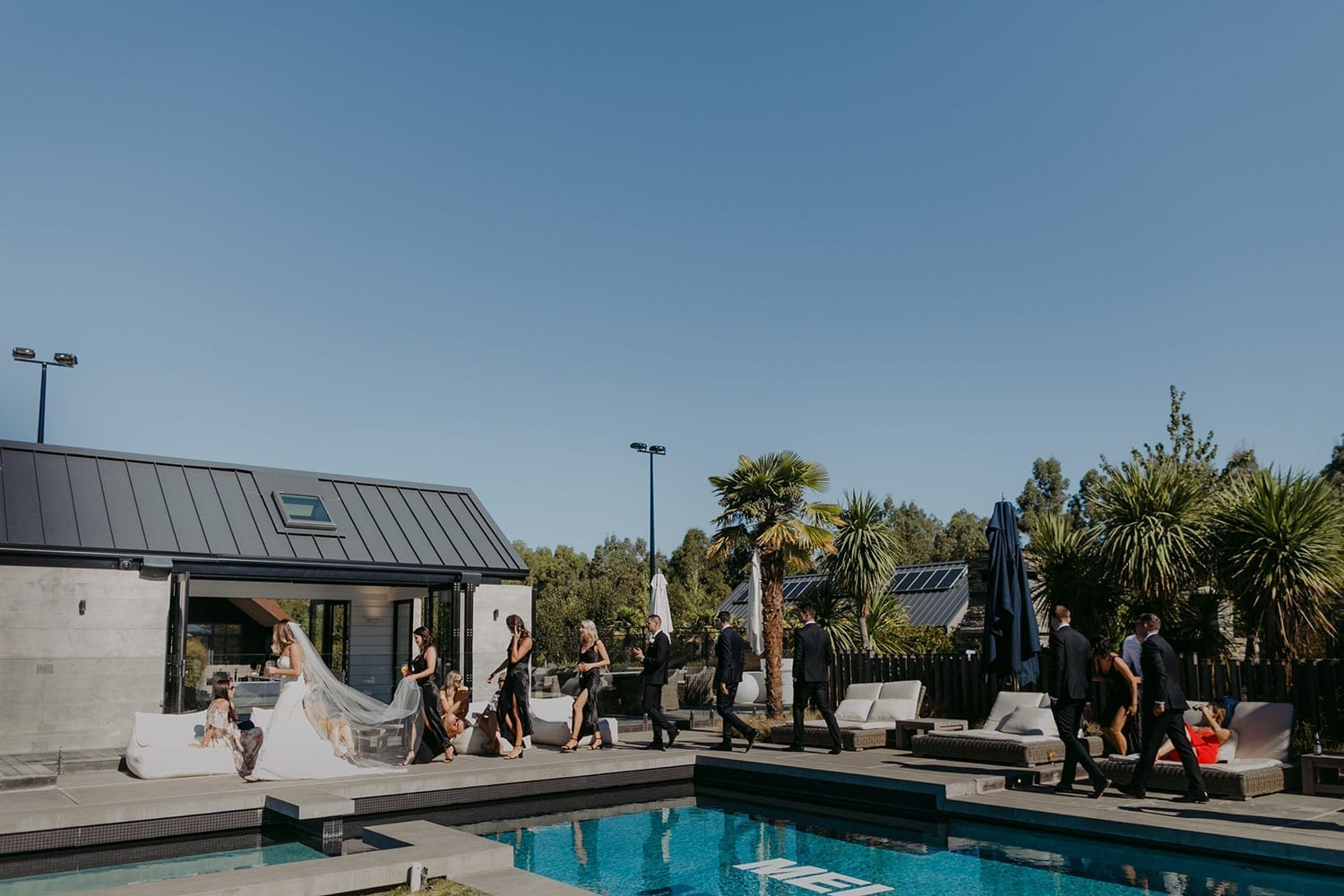 Vinka Design Features Real Weddings - bride in custom made gown, a combination of our Indi wedding dress with added beading appliqued and sewn by hand, over the top of a nude semi sheer base. With guests outdoors by pool