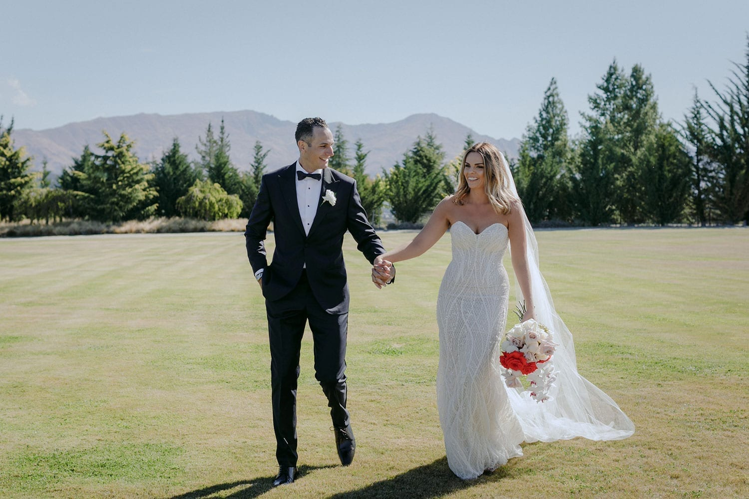 Vinka Design Features Real Weddings - bride in custom made gown, a combination of our Indi wedding dress with added beading appliqued and sewn by hand, over the top of a nude semi sheer base. Walking with groom full length