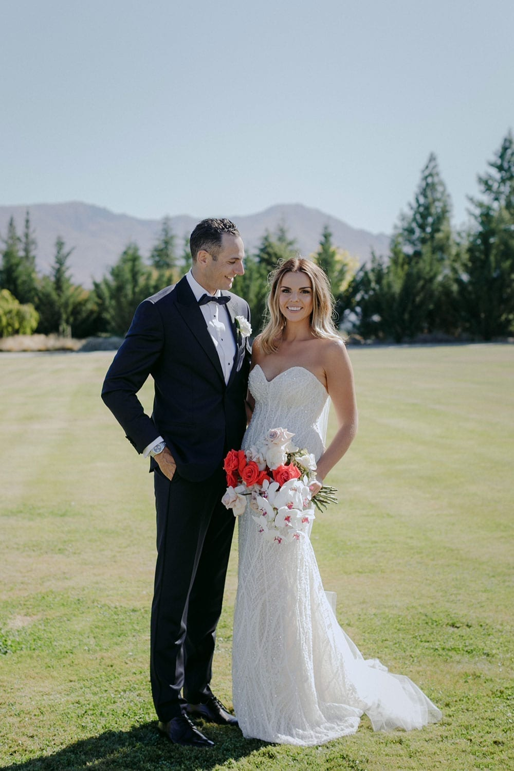 Vinka Design Features Real Weddings - bride in custom made gown, a combination of our Indi wedding dress with added beading appliqued and sewn by hand, over the top of a nude semi sheer base. Holding bouquet with groom