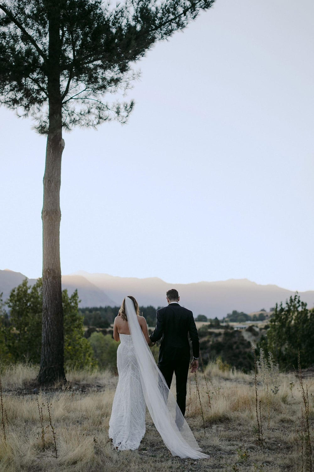 Vinka Design Features Real Weddings - bride in custom made gown, a combination of our Indi wedding dress with added beading appliqued and sewn by hand, over the top of a nude semi sheer base. Walking at sunset with groom