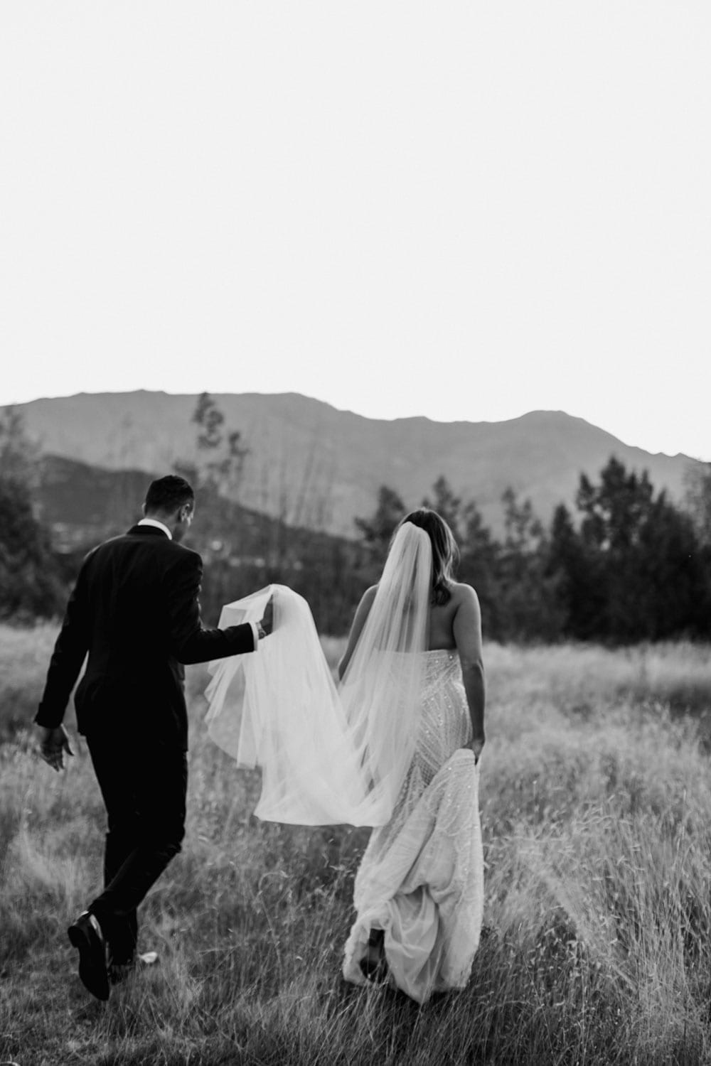 Vinka Design Features Real Weddings - bride in custom made gown, a combination of our Indi wedding dress with added beading appliqued and sewn by hand, over the top of a nude semi sheer base. Walking with groom in woods in black and white