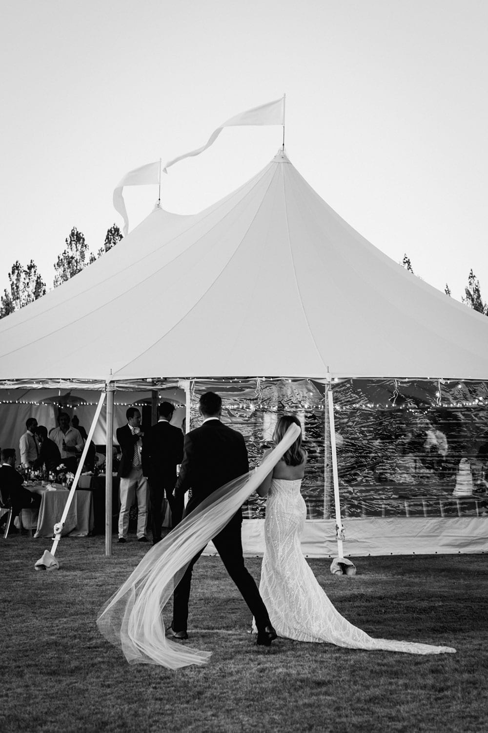 Vinka Design Features Real Weddings - bride in custom made gown, a combination of our Indi wedding dress with added beading appliqued and sewn by hand, over the top of a nude semi sheer base. Walking with groom and marquee in black and white