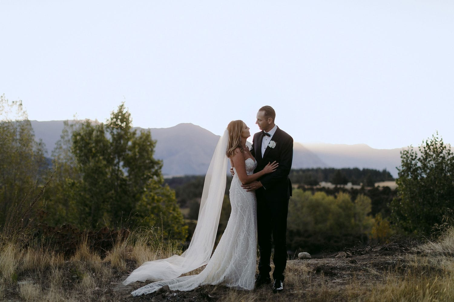 Vinka Design Features Real Weddings - bride in custom made gown, a combination of our Indi wedding dress with added beading appliqued and sewn by hand, over the top of a nude semi sheer base. Embrace with groom outdoors