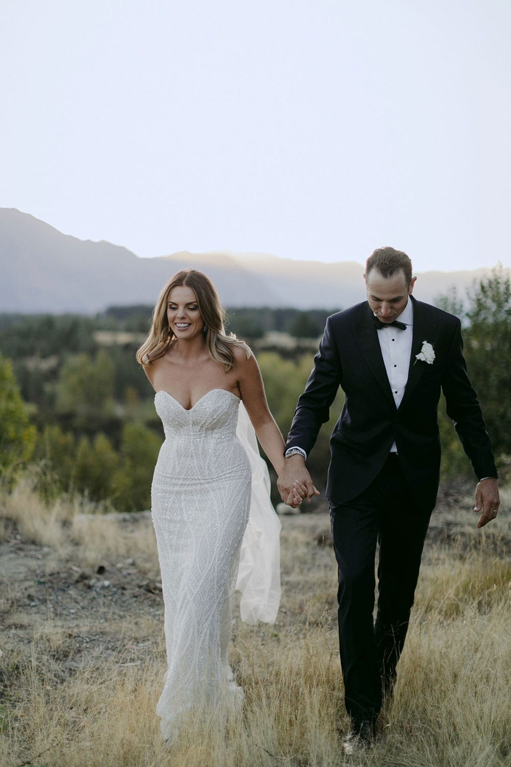 Vinka Design Features Real Weddings - bride in custom made gown, a combination of our Indi wedding dress with added beading appliqued and sewn by hand, over the top of a nude semi sheer base. Walking with groom outdoors in Queenstown