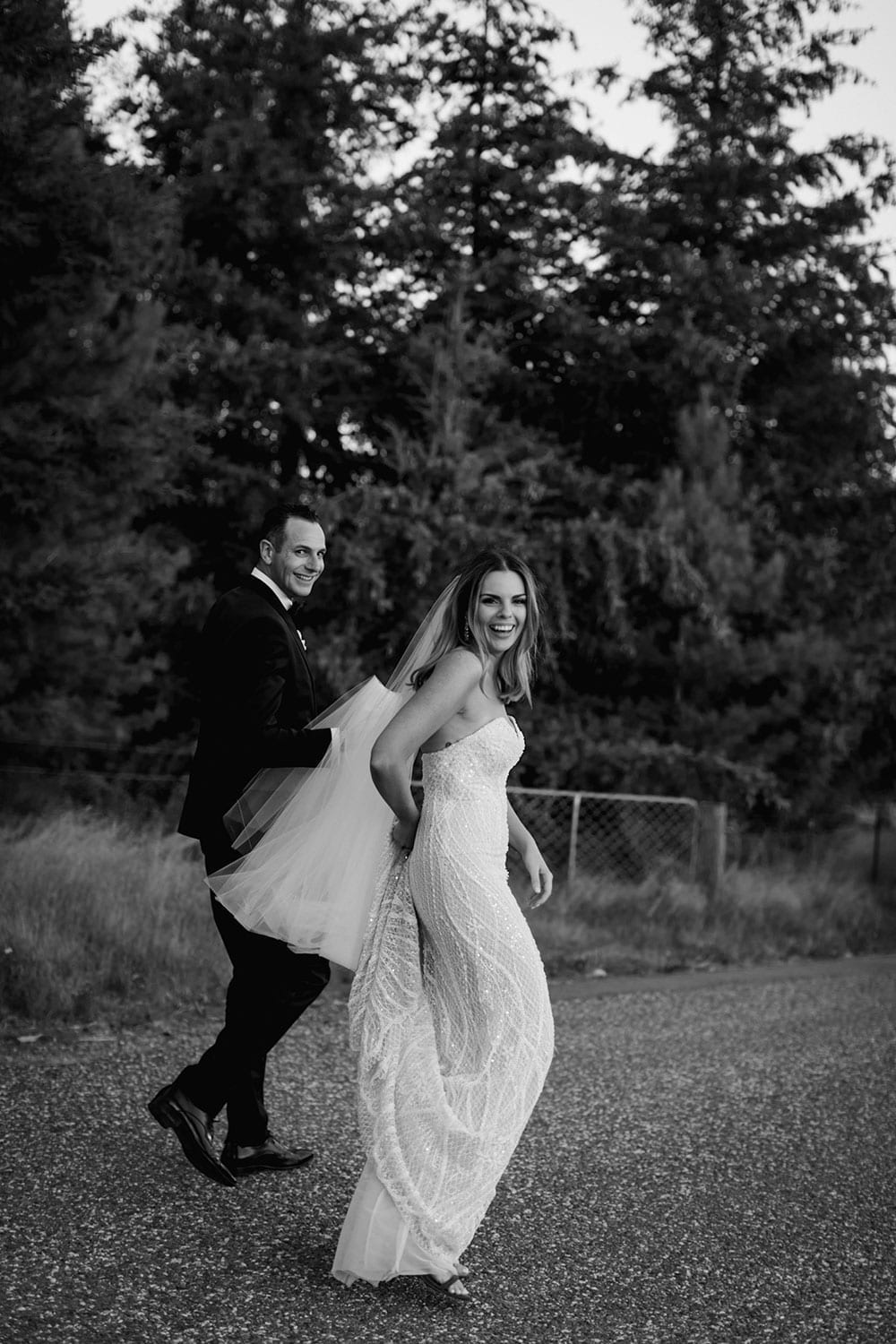 Vinka Design Features Real Weddings - bride in custom made gown, a combination of our Indi wedding dress with added beading appliqued and sewn by hand, over the top of a nude semi sheer base. Walking with groom outdoors in black and white