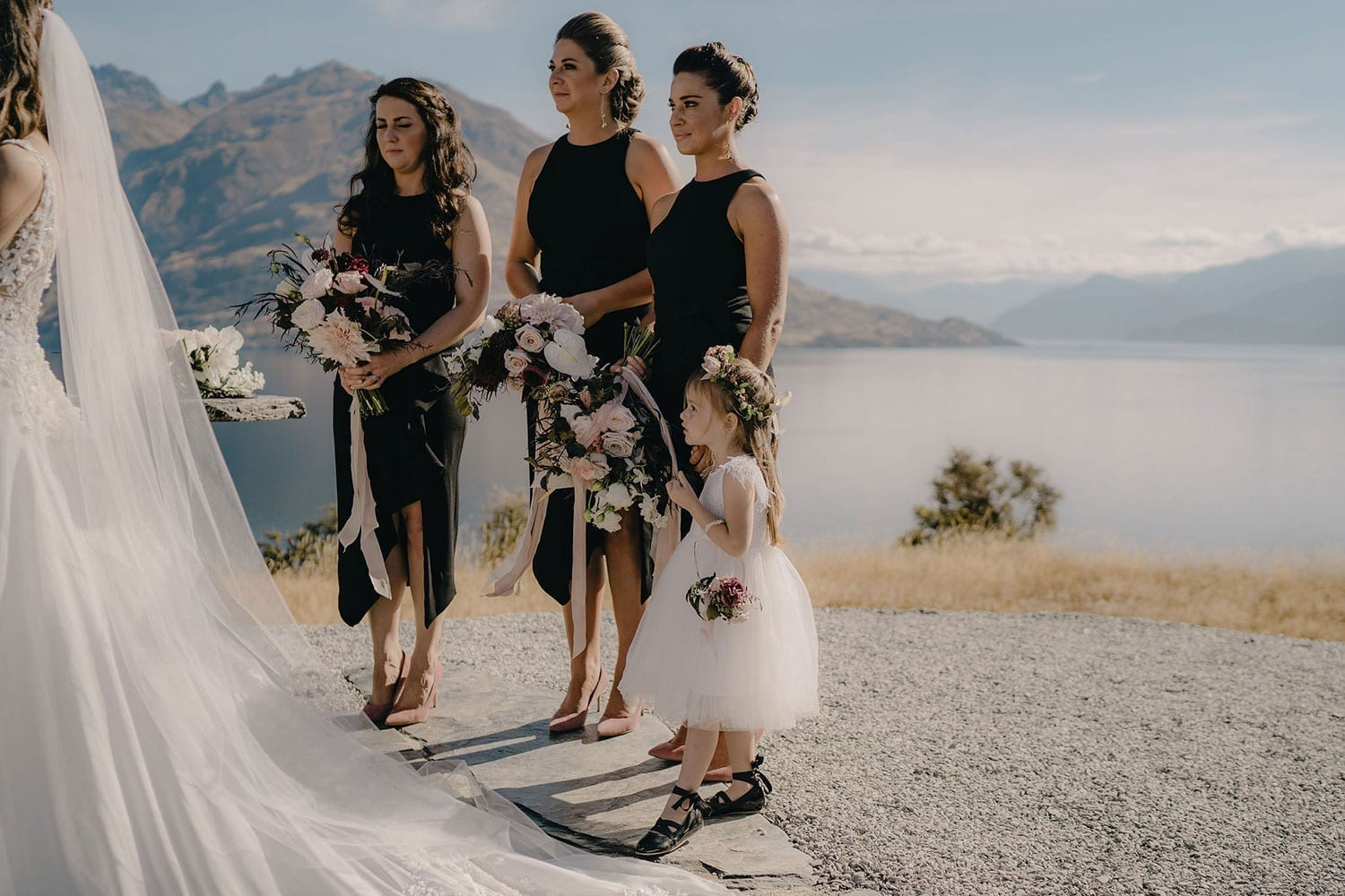 Vinka Design Features Real Weddings - bride in custom made gown, a beautiful intricate, sheer lace bodice, with a flowing, detachable, silk chiffon and tulle overskirt. The skirt had hand appliqued lace strategically placed throughout and trailing up from the train. Bridesmaids at ceremony