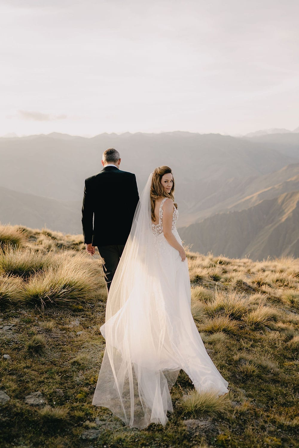 Vinka Design Features Real Weddings - bride in custom made gown, a beautiful intricate, sheer lace bodice, with a flowing, detachable, silk chiffon and tulle overskirt. The skirt had hand appliqued lace strategically placed throughout and trailing up from the train. Walking with groom looking back along mountain in NZ