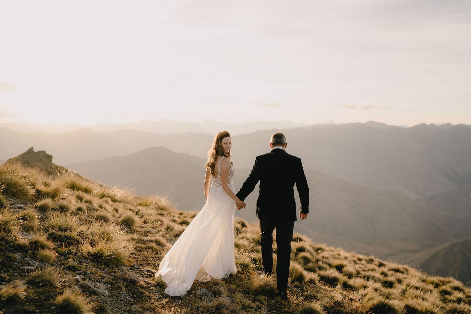 Vinka Design Features Real Weddings - bride in custom made gown, a beautiful intricate, sheer lace bodice, with a flowing, detachable, silk chiffon and tulle overskirt. The skirt had hand appliqued lace strategically placed throughout and trailing up from the train. Walking with groom looking over shoulder on mountain in NZ