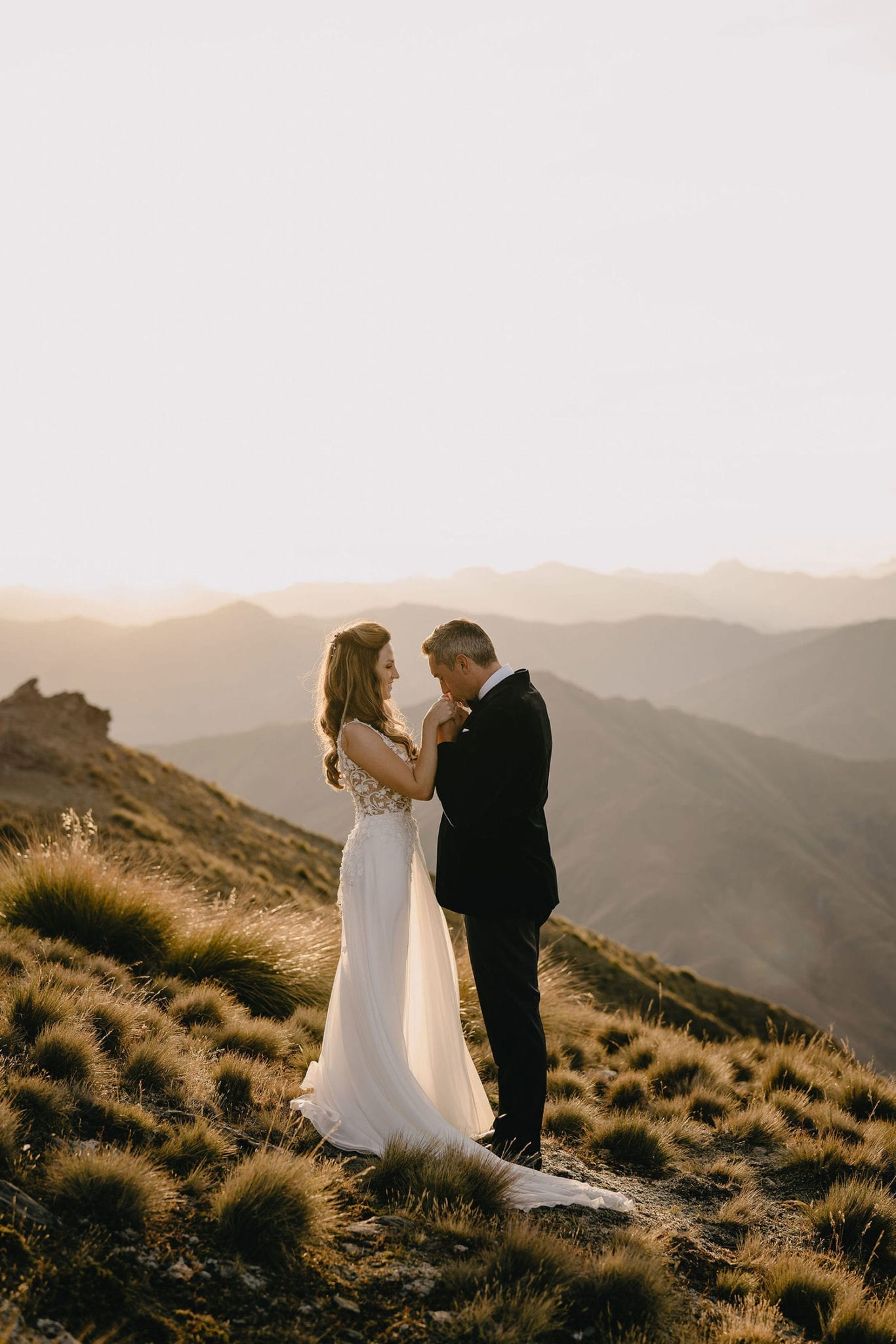 Vinka Design Features Real Weddings - bride in custom made gown, a beautiful intricate, sheer lace bodice, with a flowing, detachable, silk chiffon and tulle overskirt. The skirt had hand appliqued lace strategically placed throughout and trailing up from the train. Walking with groom embracing on mountain in NZ