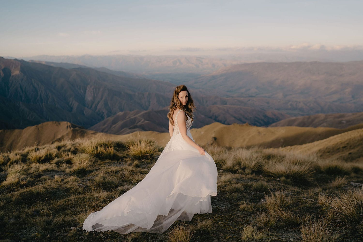 Vinka Design Features Real Weddings - bride in custom made gown, a beautiful intricate, sheer lace bodice, with a flowing, detachable, silk chiffon and tulle overskirt. The skirt had hand appliqued lace strategically placed throughout and trailing up from the train. On mountain in NZ with dress flowing behind