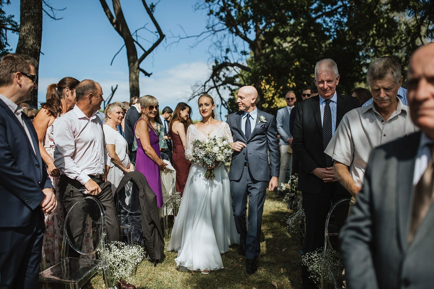 Vinka Design Features Real Weddings - Bride in custom made gown with bold lace bodice with fitted, long, beaded lace sleeves. Walking down aisle outdoors