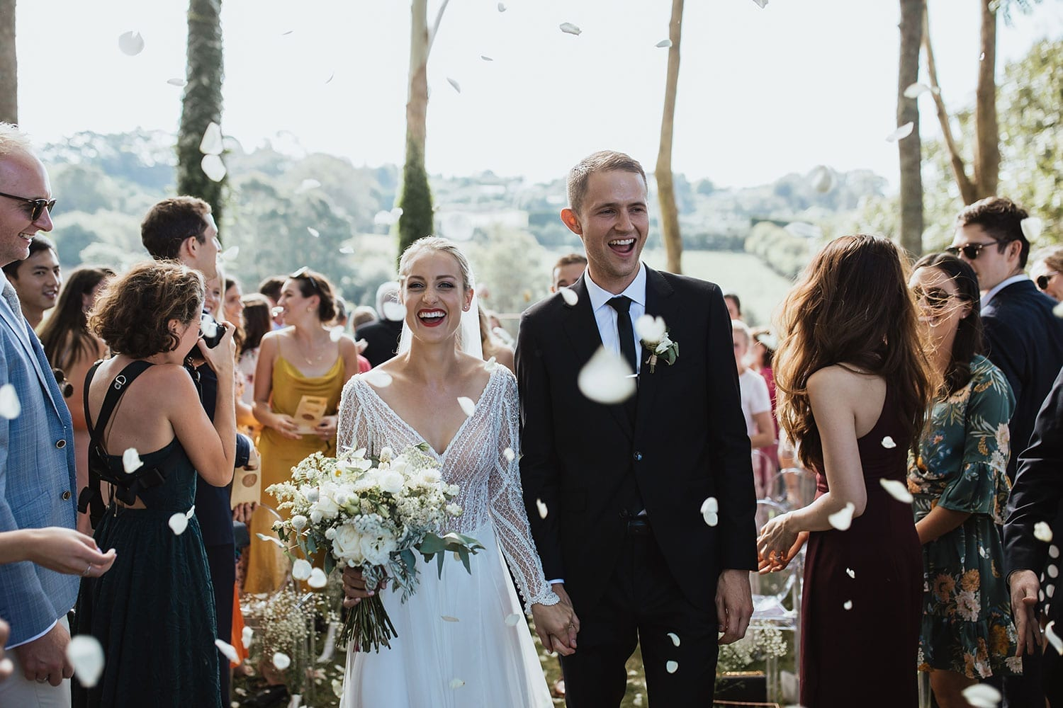 Vinka Design Features Real Weddings - Bride in custom made gown with bold lace bodice with fitted, long, beaded lace sleeves. Kiss the bride. Just married - with confetti