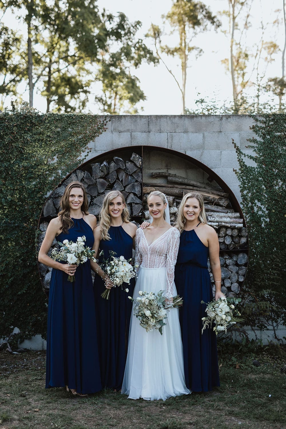 Vinka Design Features Real Weddings - Bride in custom made gown with bold lace bodice with fitted, long, beaded lace sleeves and floating skirt. With bridesmaids