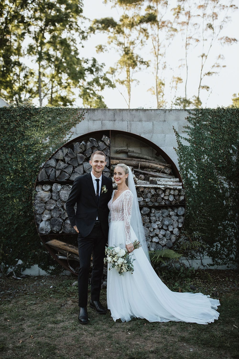 Vinka Design Features Real Weddings - Bride in custom made gown with bold lace bodice with fitted, long, beaded lace sleeves and floating skirt. With groom
