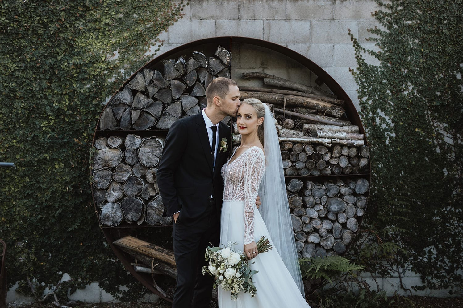 Vinka Design Features Real Weddings - Bride in custom made gown with bold lace bodice with fitted, long, beaded lace sleeves and floating skirt. With groom kissing head