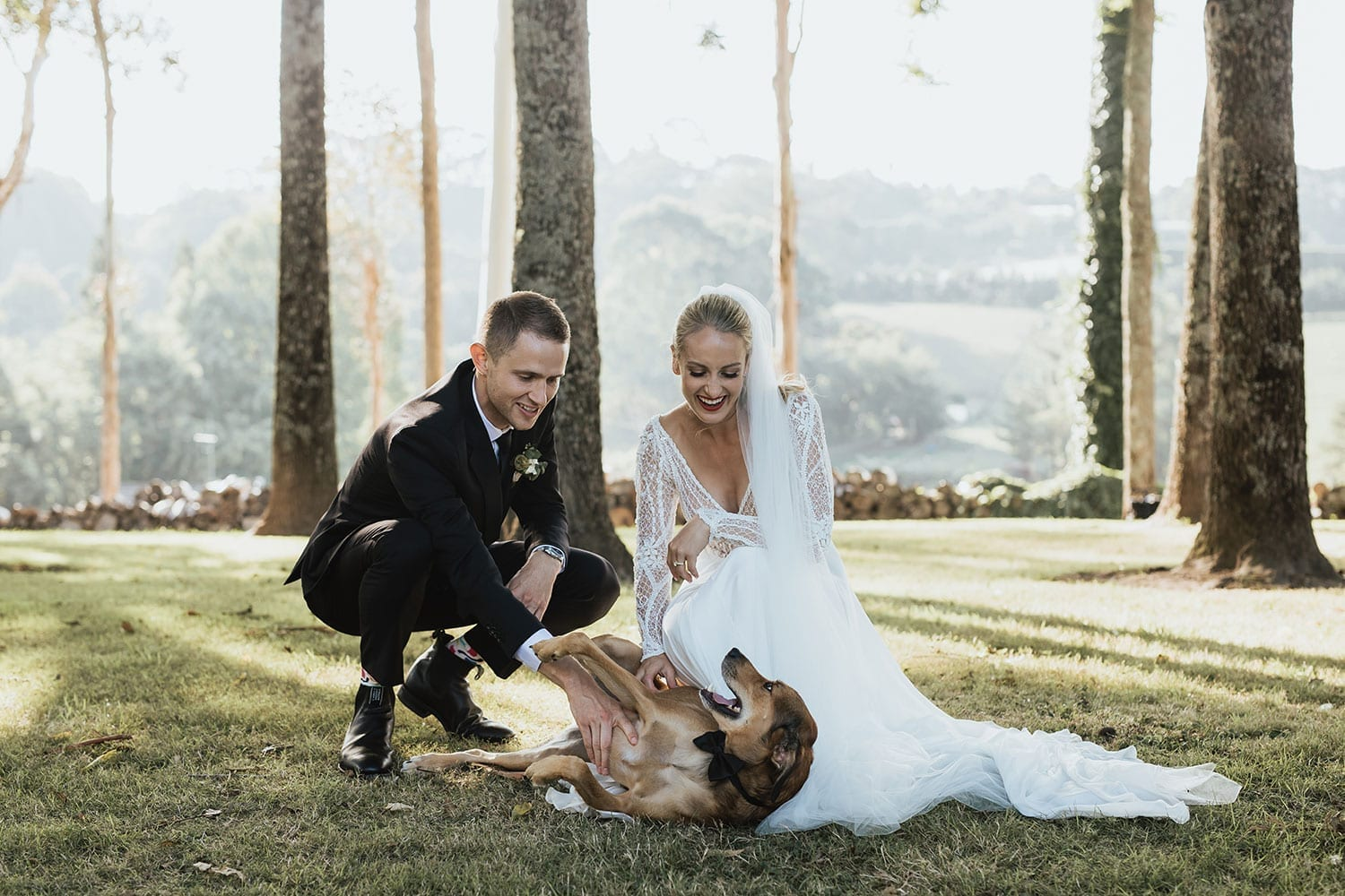 Vinka Design Features Real Weddings - Bride in custom made gown with bold lace bodice with fitted, long, beaded lace sleeves and floating skirt. With groom and dog