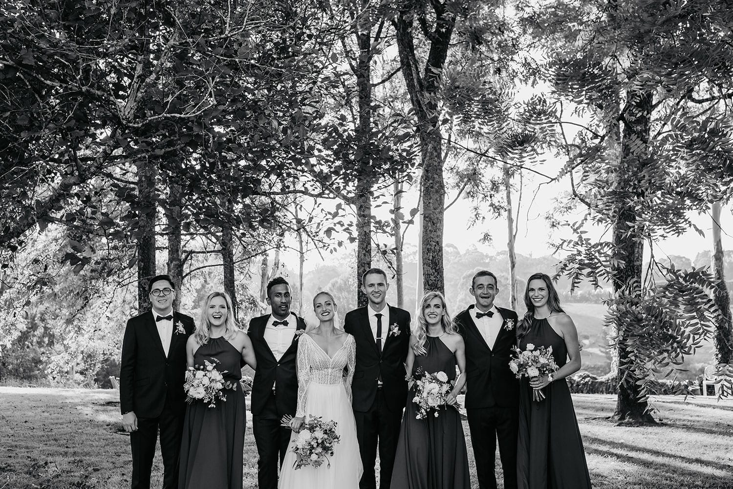 Vinka Design Features Real Weddings - Bride in custom made gown with bold lace bodice with fitted, long, beaded lace sleeves and floating skirt. With bridal party in wooded area. Black and white