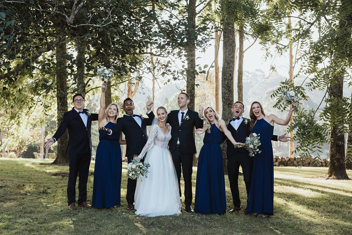Vinka Design Features Real Weddings - Bride in custom made gown with bold lace bodice with fitted, long, beaded lace sleeves and floating skirt. With bridal party in wooded area posing