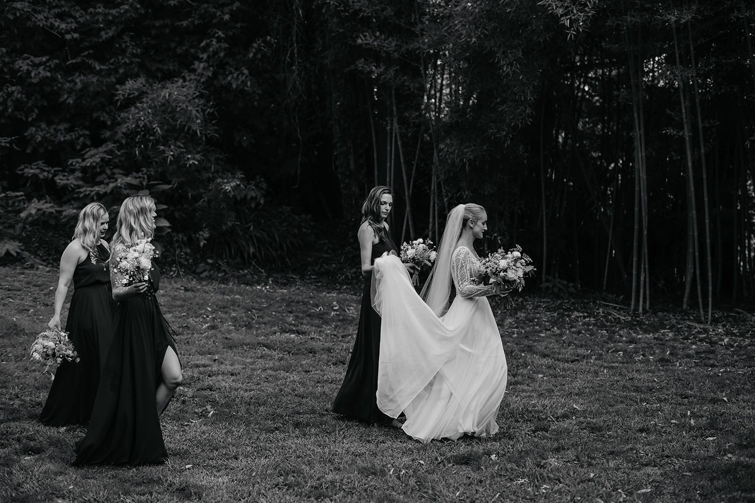 Vinka Design Features Real Weddings - Bride in custom made gown with bold lace bodice with fitted, long, beaded lace sleeves and floating skirt. With bridesmaids walking outdoors - black and white