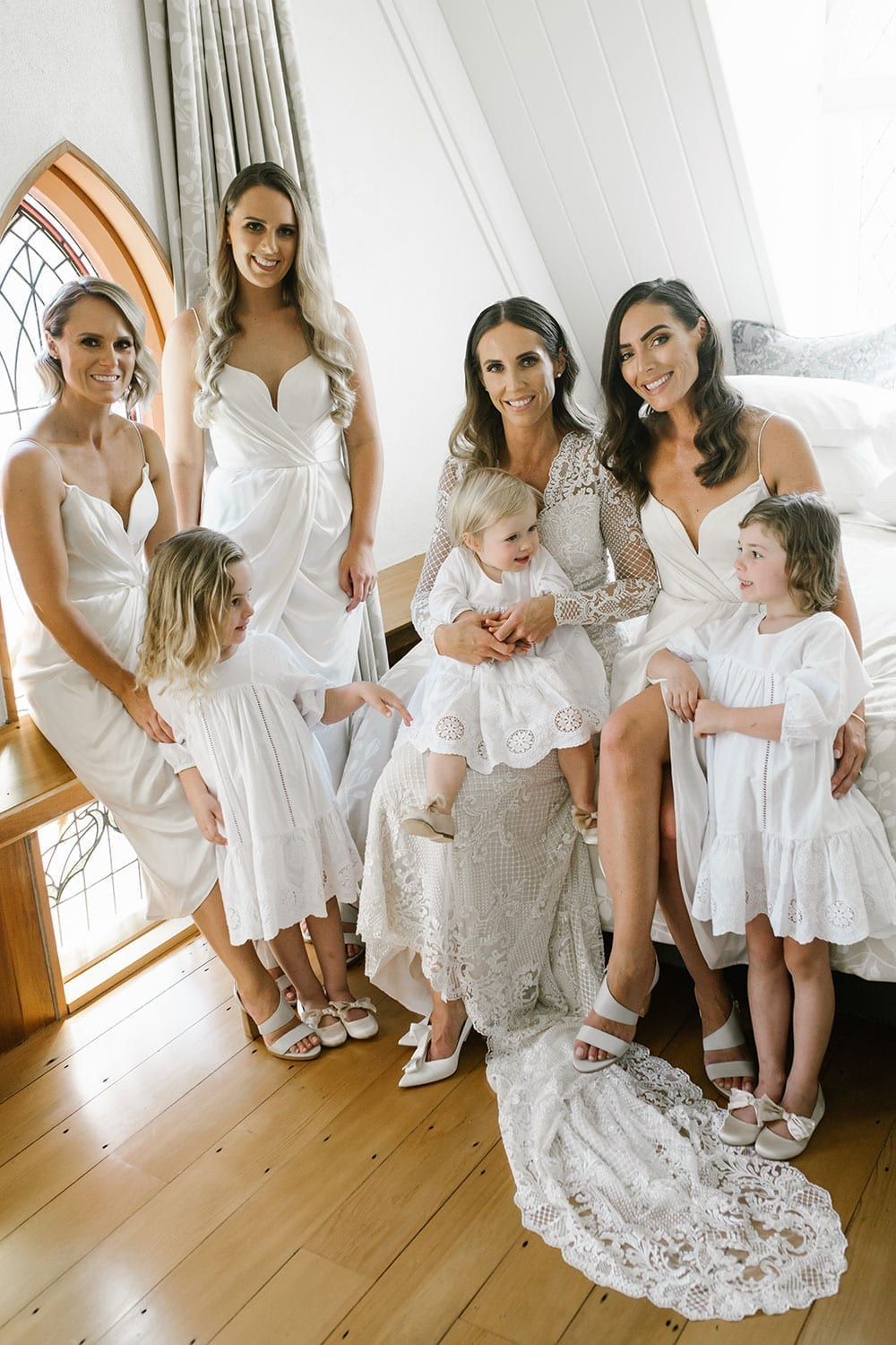 Vinka Design Features Real Weddings - Bride in bespoke fitted lace gown with bridesmaids and children before wedding