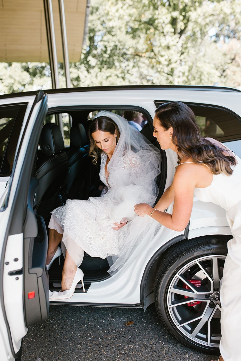 Vinka Design Features Real Weddings - Bride in bespoke fitted lace gown getting out of car
