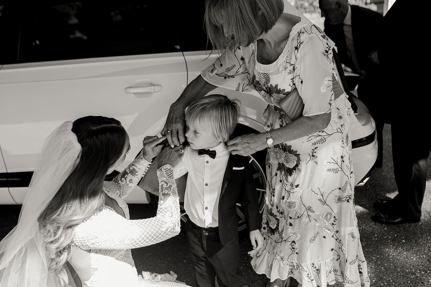 Vinka Design Features Real Weddings - Bride in bespoke fitted lace gown helping page boy into jacket