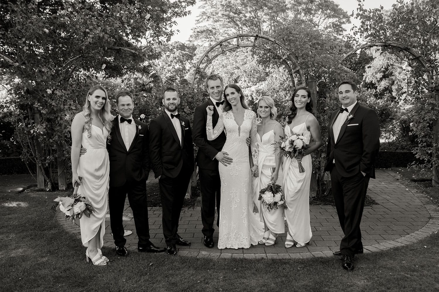 Vinka Design Features Real Weddings - Bride in bespoke fitted lace gown with deep v neck. With bridal party in garden