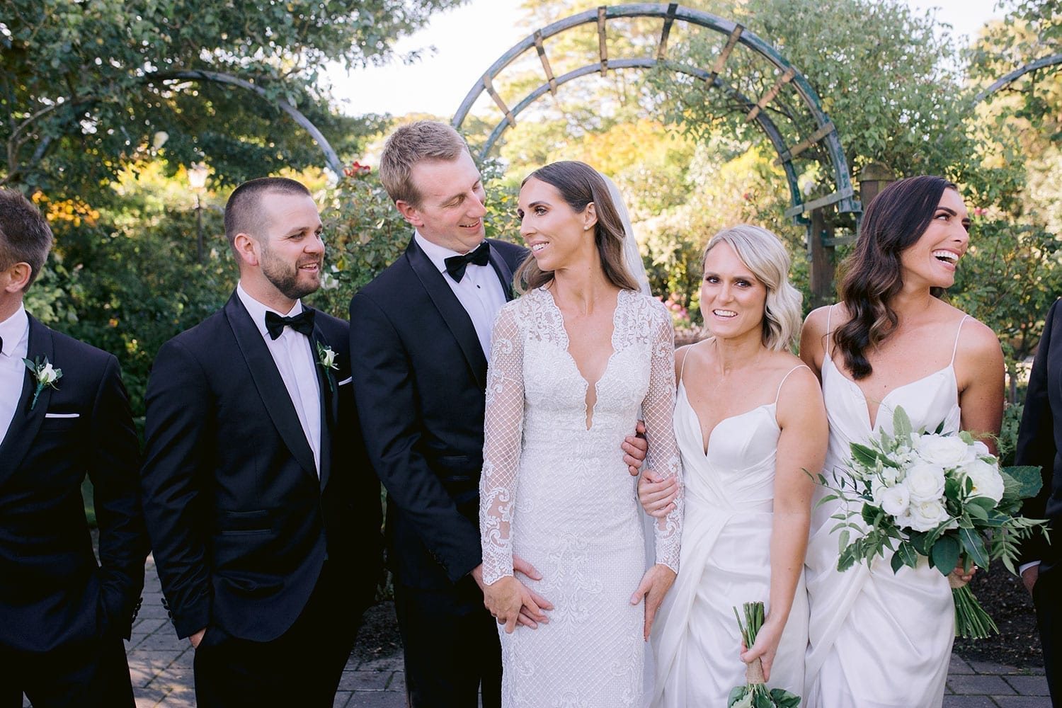 Vinka Design Features Real Weddings - Bride in bespoke fitted lace gown with deep v neck. Laughing with bridal party in garden
