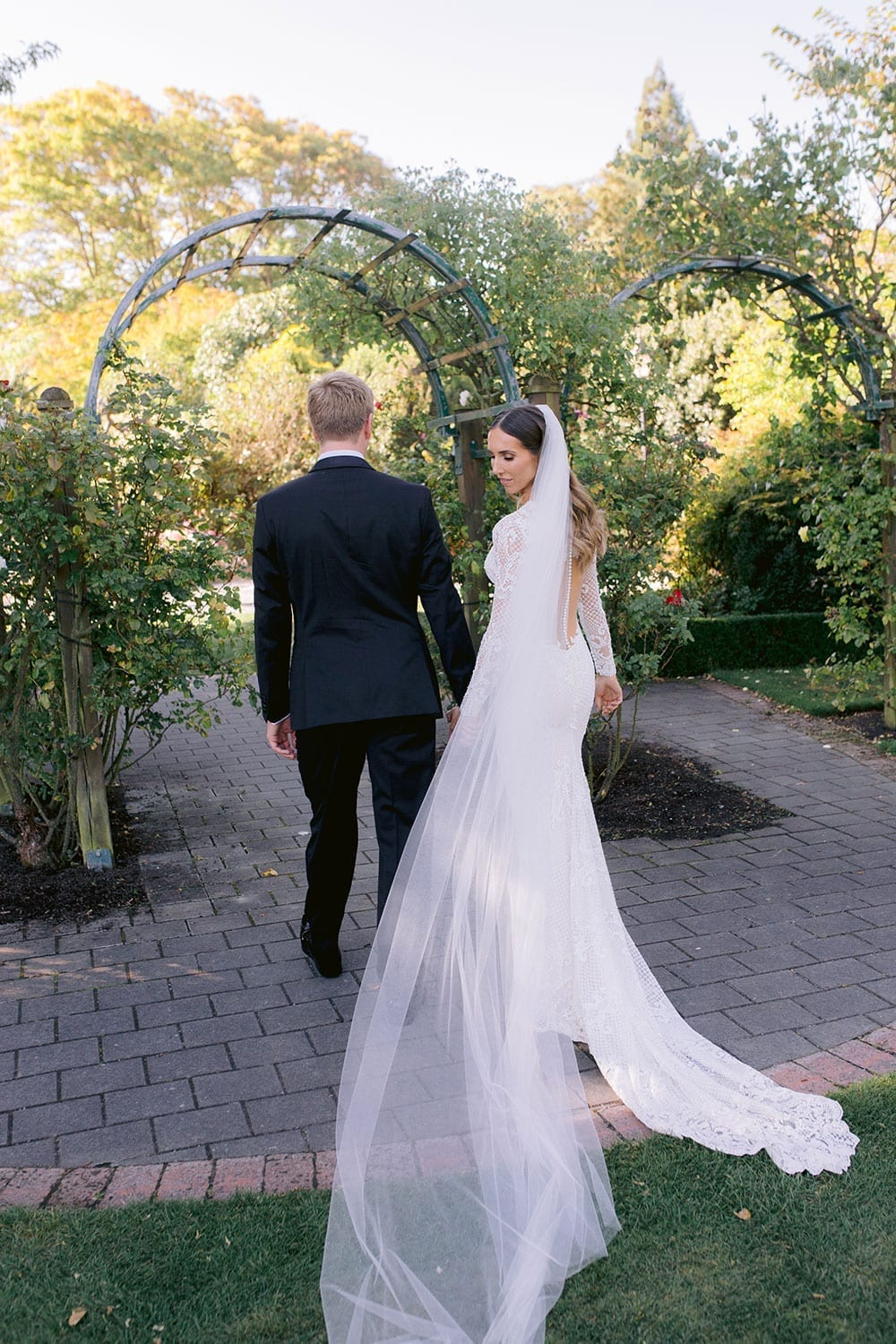 Vinka Design Features Real Weddings - Bride in bespoke fitted lace gown with deep v neck. Walking with groom, dress train and veil falling behind