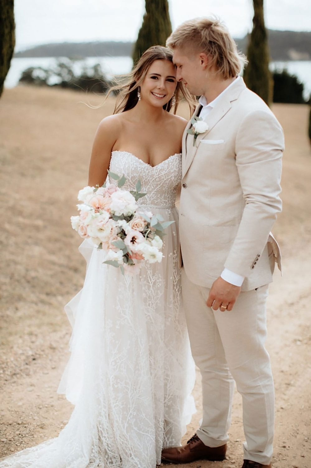 Vinka Design Features Real Weddings - bride wearing custom made strapless beaded lace dress. Bride and groom pose outdoors