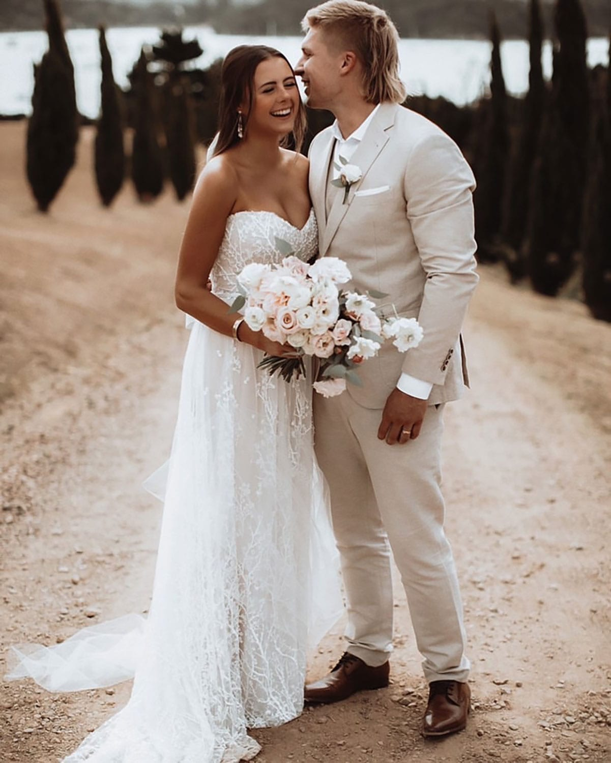 Vinka Design Features Real Weddings - bride wearing custom made strapless beaded lace dress. Bride and groom share a laugh