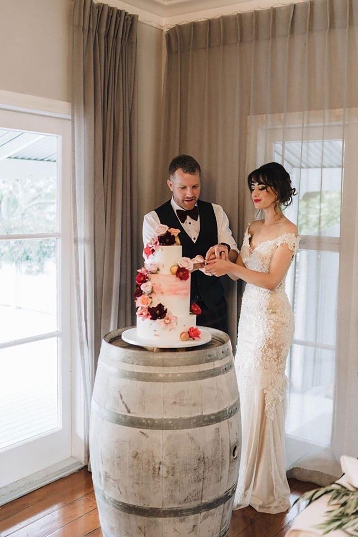 Vinka Design Features Real Weddings - bride wearing custom made beaded lace Sasha gown. Cutting wedding cake