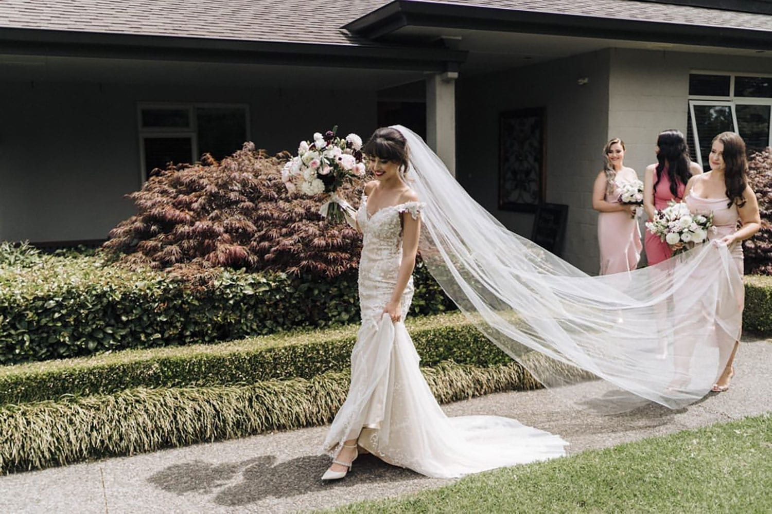 Vinka Design Features Real Weddings - bride wearing custom made beaded lace Sasha gown. Bride walks with dress train flowing and long veil held by bridesmaid
