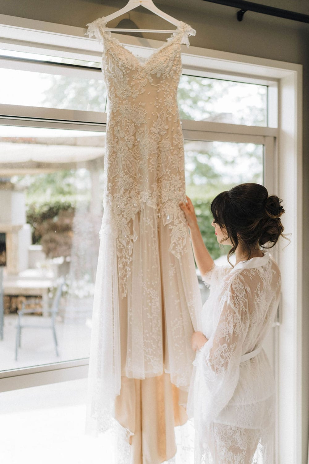 Vinka Design Features Real Weddings - bride wearing custom made beaded lace Sasha gown. Bride looks at hanging dress