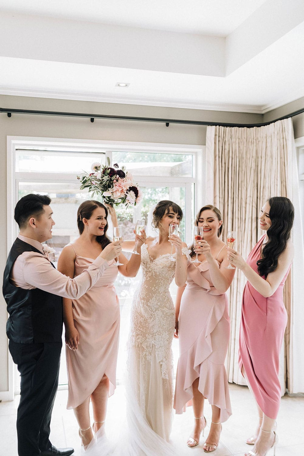 Vinka Design Features Real Weddings - bride wearing custom made beaded lace Sasha gown. Bride cheers with bridal party