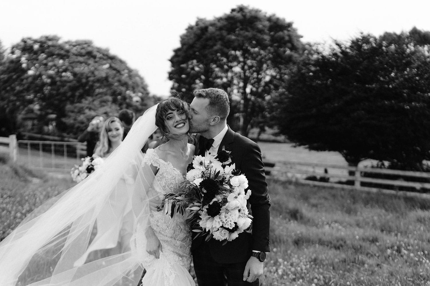 Vinka Design Features Real Weddings - bride wearing custom made beaded lace Sasha gown. Groom kisses bride in field, black and white