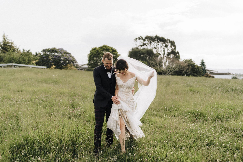 Vinka Design Features Real Weddings - bride wearing custom made beaded lace Sasha gown. Groom walks bride through field
