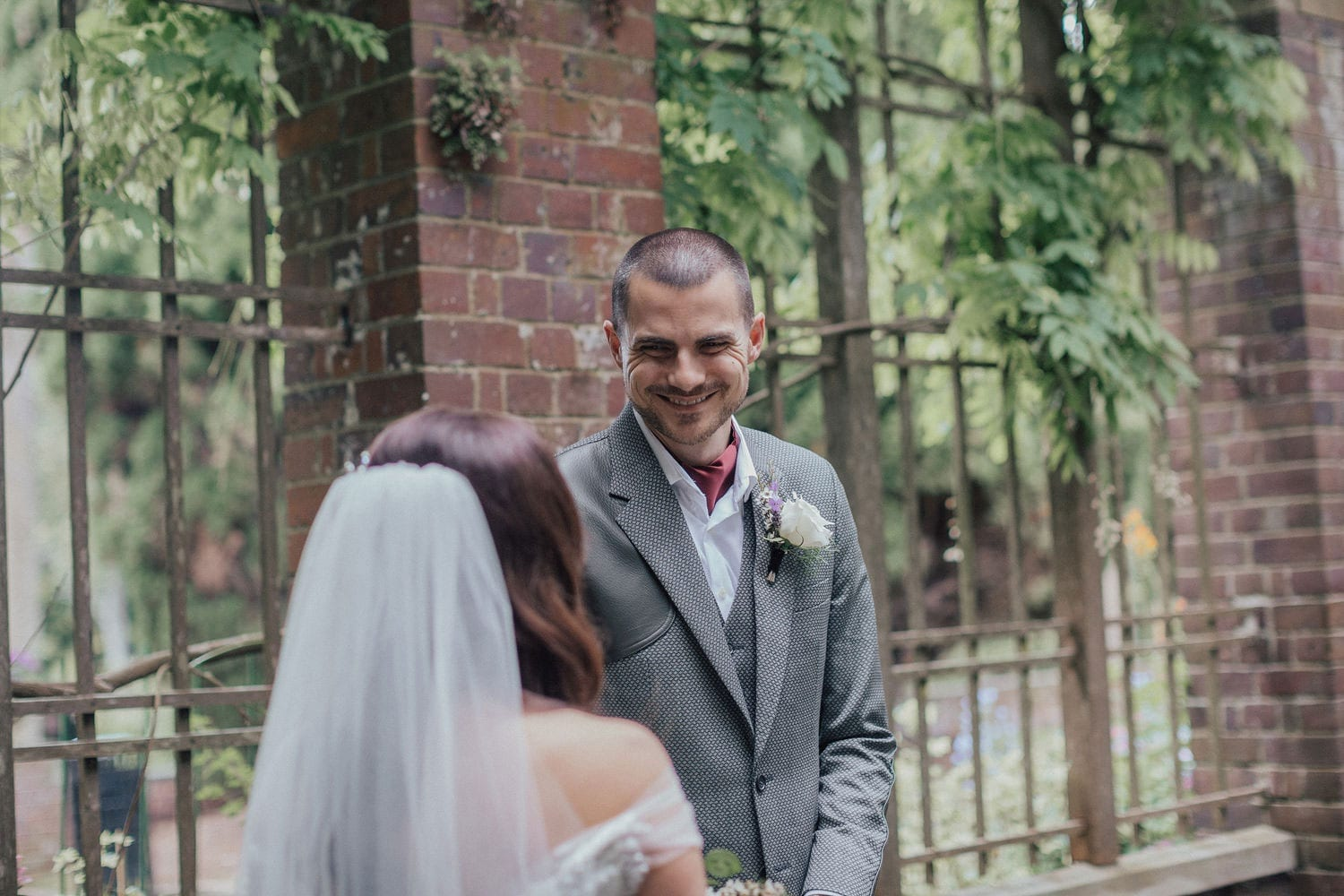 Vinka Design Features Real Weddings - bride wearing custom made lace wedding gown. Smiling groom looks at bride