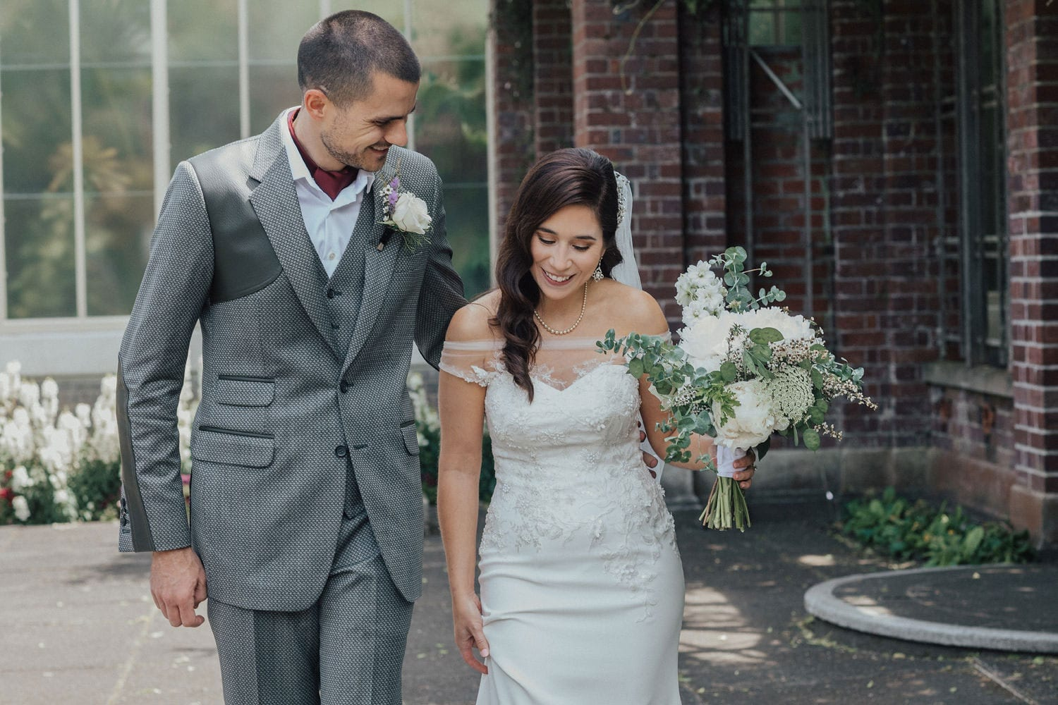 Vinka Design Features Real Weddings - bride wearing custom made lace wedding gown. Bride and groom walk