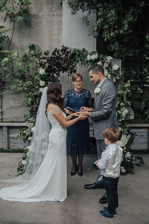 Vinka Design Features Real Weddings - bride wearing custom made lace wedding gown. Bride and groom exchange rings