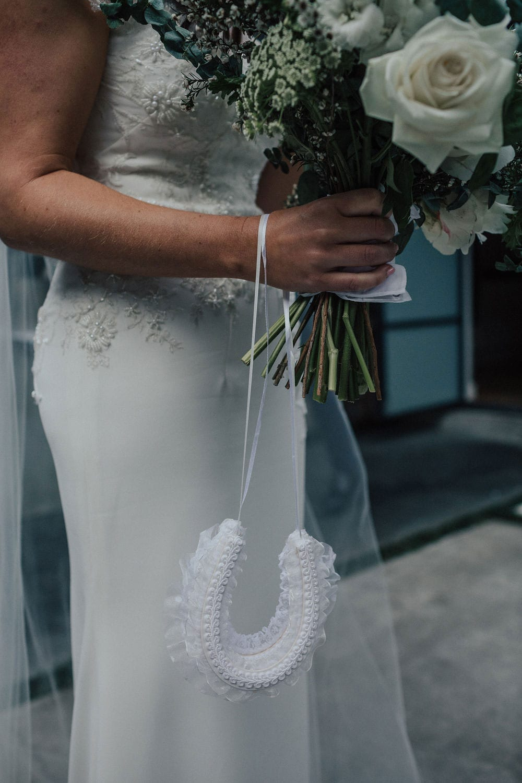 Vinka Design Features Real Weddings - bride wearing custom made lace wedding gown. Horse shoe, bouquet, sleek dress silhouette