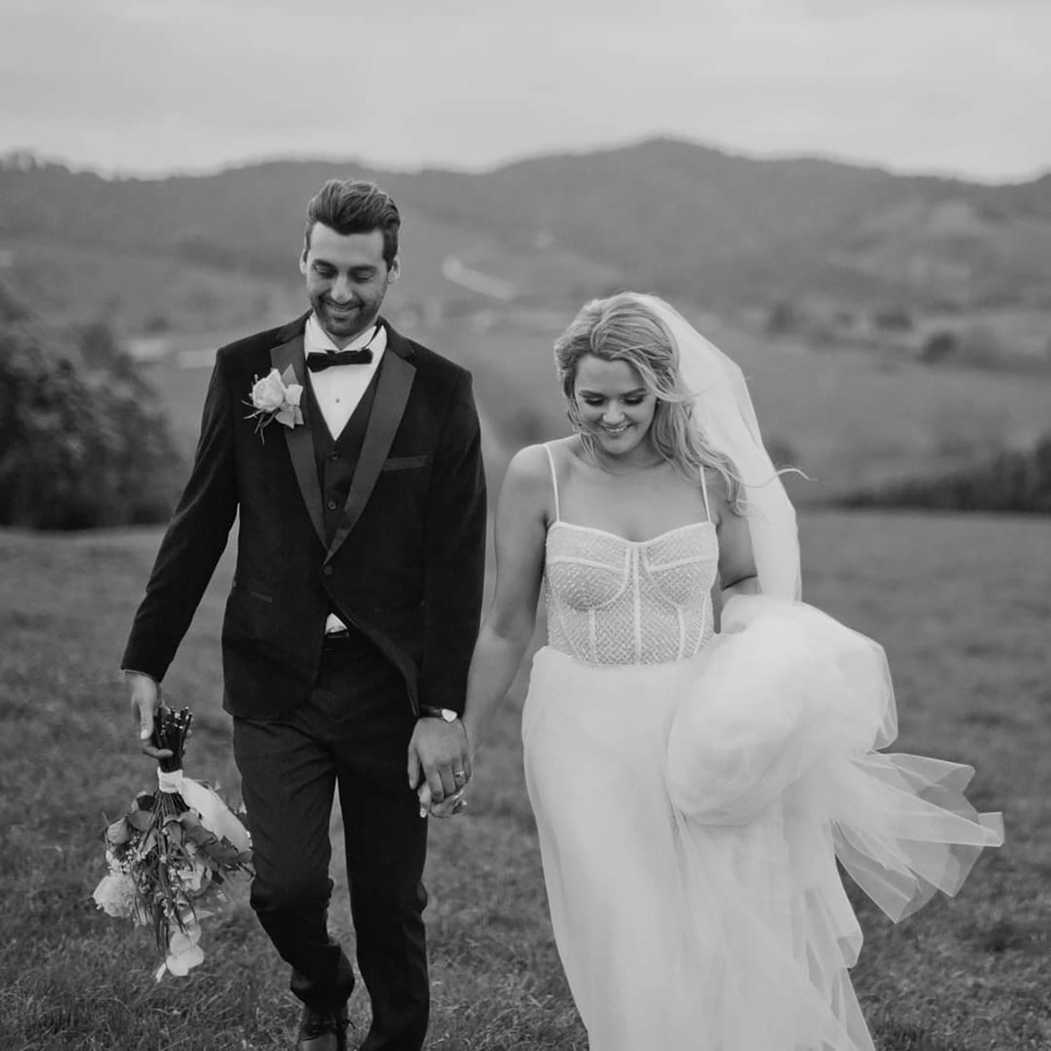 Vinka Design Features Real Weddings - bride wearing custom made gown with two different beadings incorporated into a fitted, structured bodice, and dreamy layered tulle skirt. Bride and groom walk through field in black and white