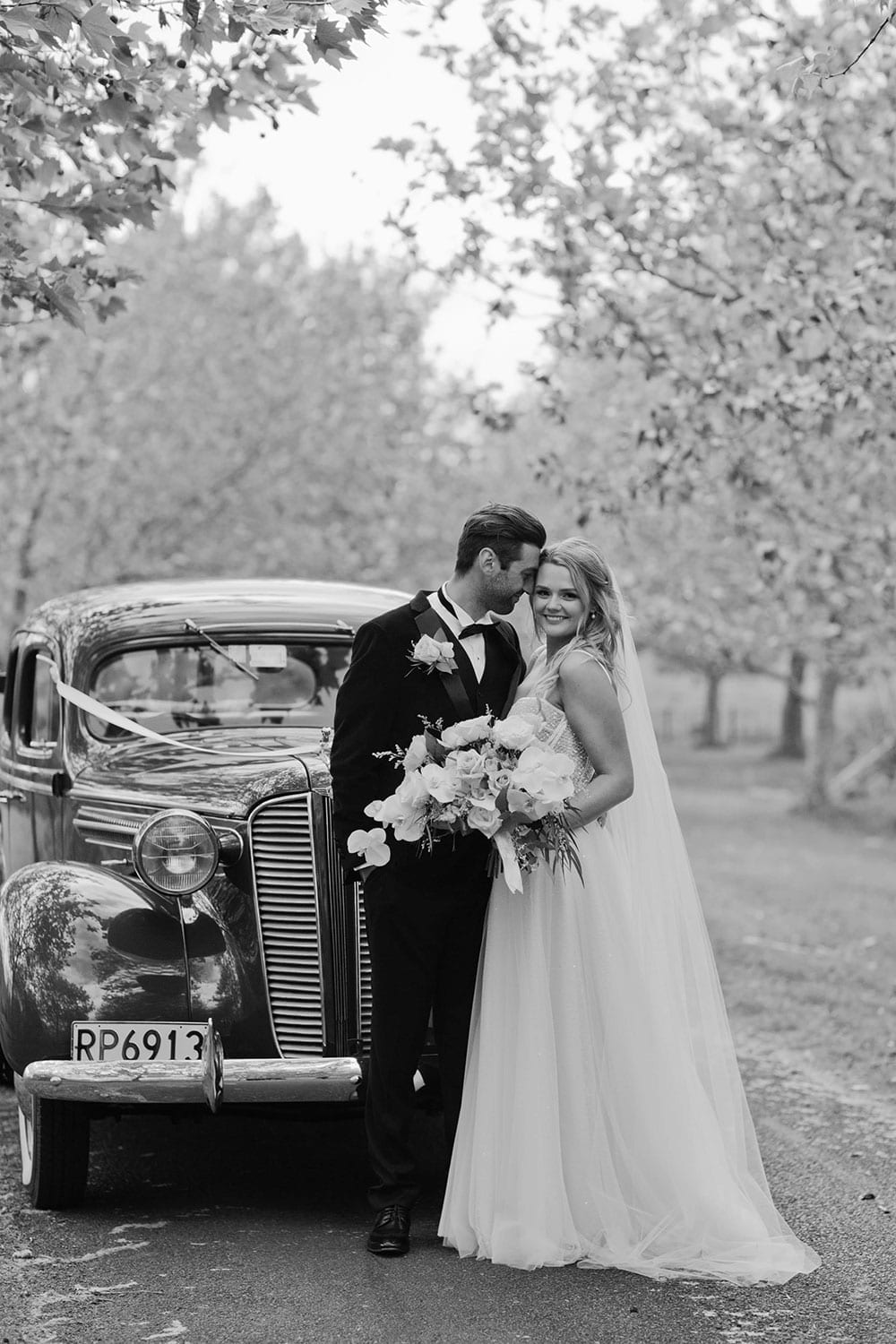 Vinka Design Features Real Weddings - bride wearing custom made gown with two different beadings incorporated into a fitted, structured bodice, and dreamy layered tulle skirt. Bride and groom head to head next to wedding car in black and white