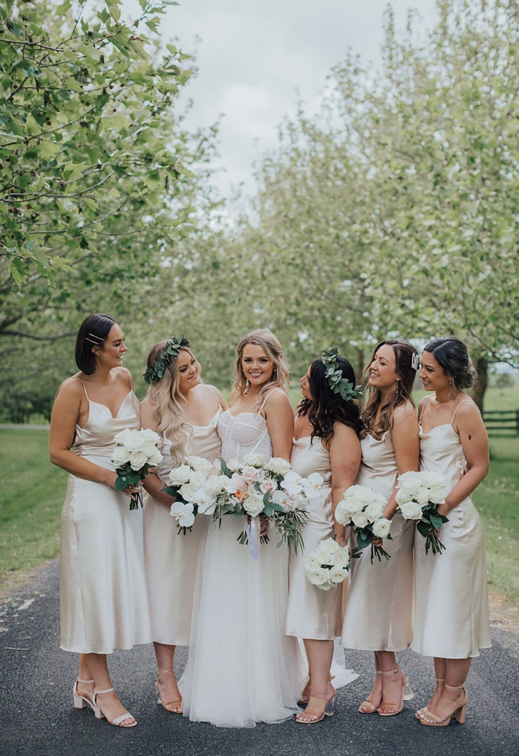 Vinka Design Features Real Weddings - bride wearing custom made gown with two different beadings incorporated into a fitted, structured bodice, and dreamy layered tulle skirt. Bride and bridesmaids surrounded by blossom