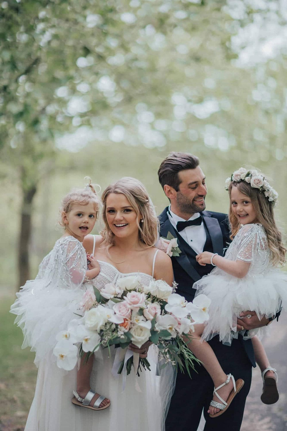 Vinka Design Features Real Weddings - bride wearing custom made gown with two different beadings incorporated into a fitted, structured bodice, and dreamy layered tulle skirt. Bride and groom with children in blossom trees