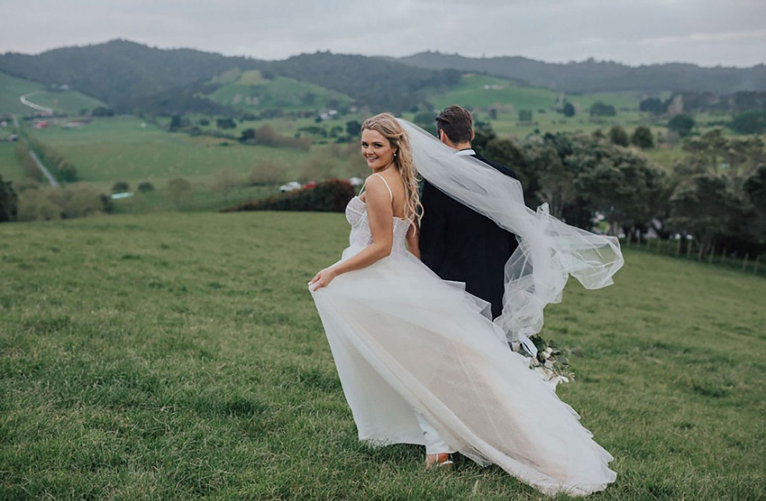 Vinka Design Features Real Weddings - bride wearing custom made gown with two different beadings incorporated into a fitted, structured bodice, and dreamy layered tulle skirt. Bride and groom walk through field with dress and veil blowing in the breeze