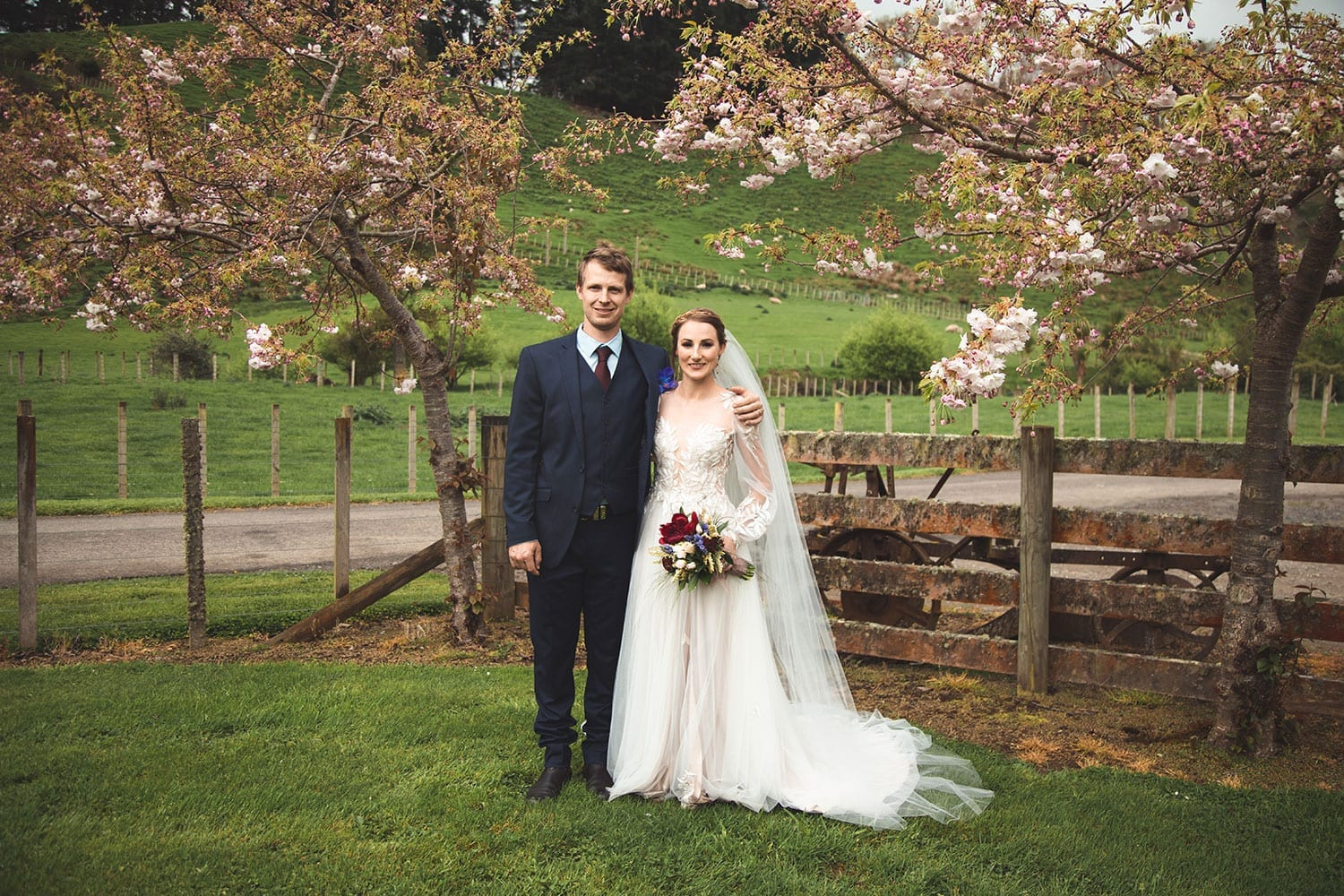 Vinka Design Features Real Weddings - bride in custom made gown, a combination of Isabelle and Ivy from our Heart of Havana collection. Bride and groom pose in field