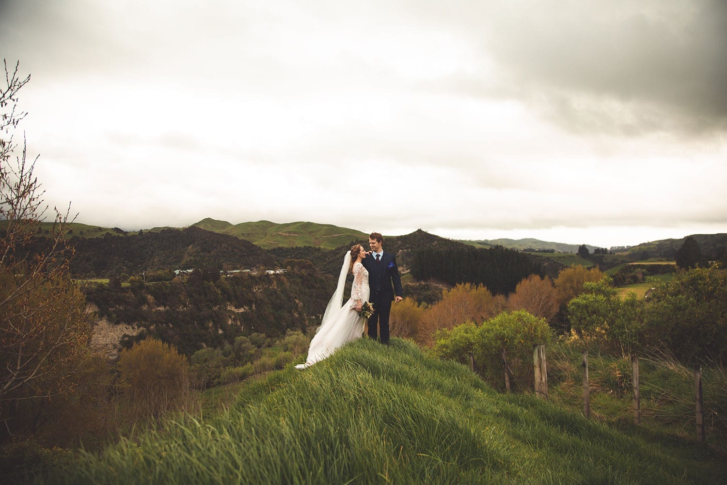 Vinka Design Features Real Weddings - bride in custom made gown, a combination of Isabelle and Ivy from our Heart of Havana collection. Bride and groom in a field with panoramic views