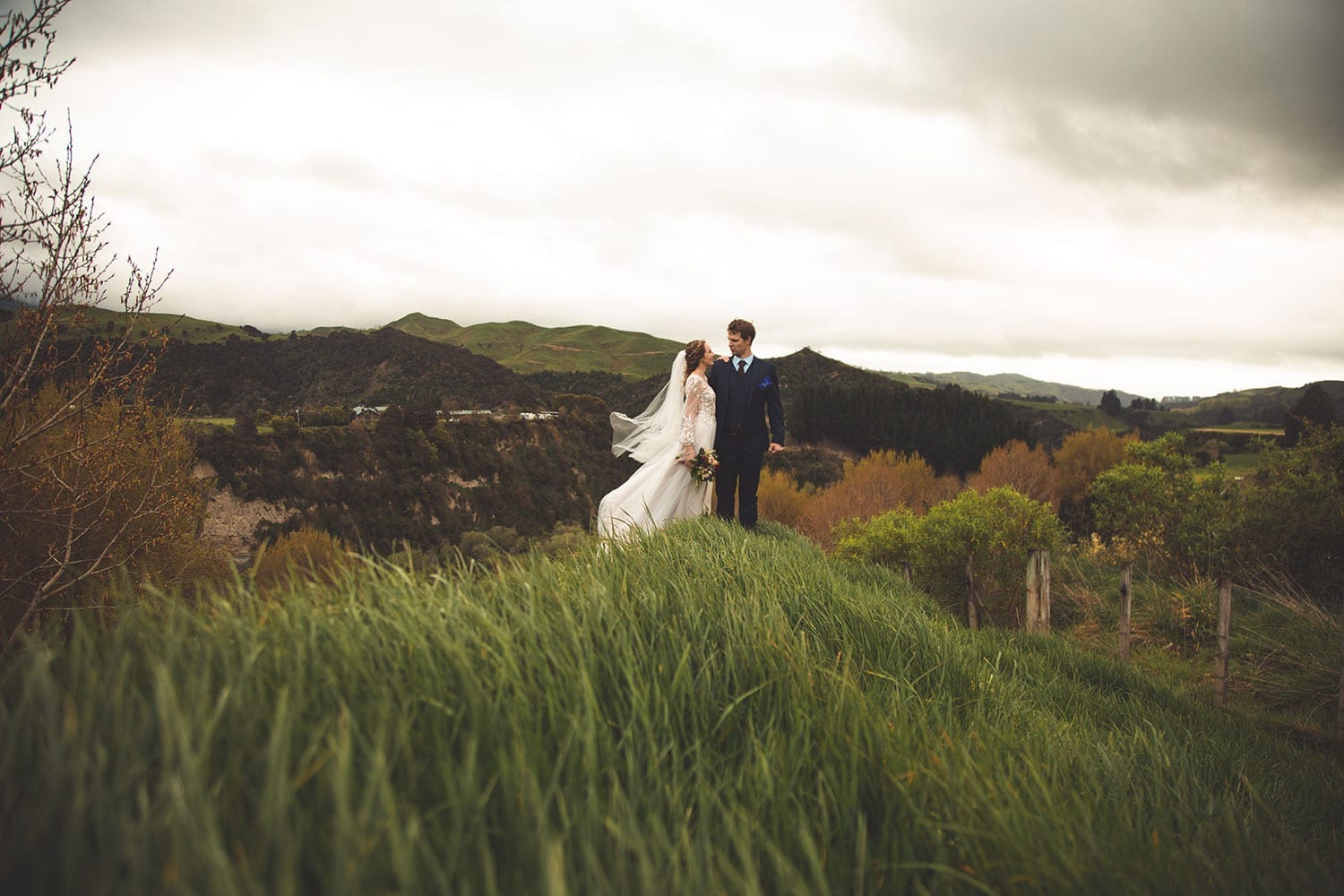Vinka Design Features Real Weddings - bride in custom made gown, a combination of Isabelle and Ivy from our Heart of Havana collection. Bride and groom in a field with panormaic views